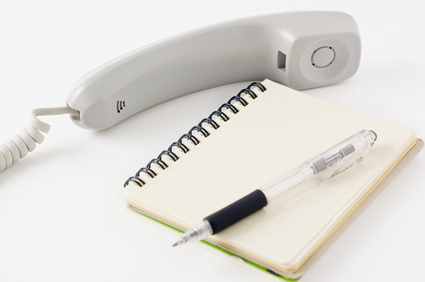 受話器とメモ帳と鉛筆
